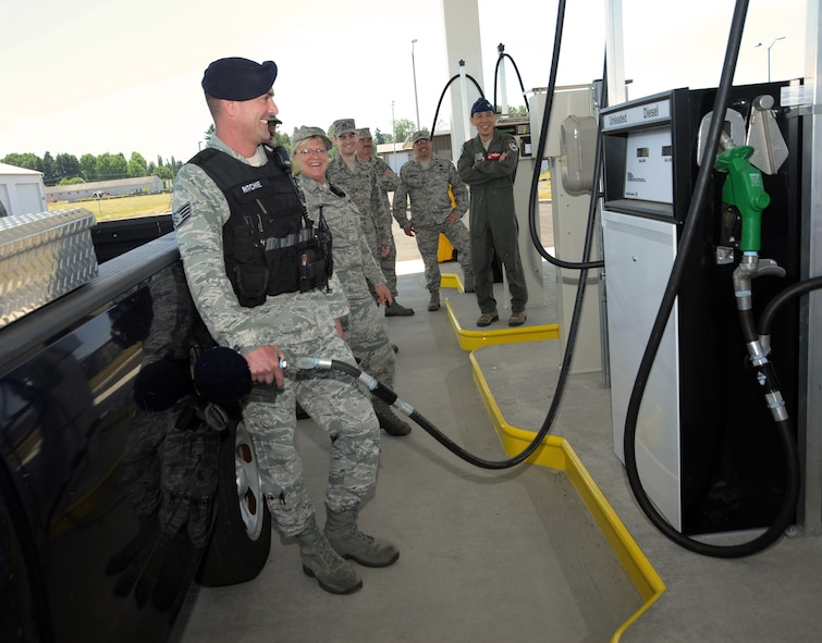 Staff Sgt. Matthew Ritchie, assigned to the 142nd Fighter Wing Security Forces Squadron, left, is the first to fill up at the new on base service station at the Portland Air National Guard Base, June 5, 2014. Other members from the Fighter Wing enjoy the moment along with Col. Jeff Hwang, far right, 142nd Fighter Wing Vice Commander.(Air National Guard photo by Tech. Sgt. John Hughel, 142nd Fighter Wing Public Affairs/Released)