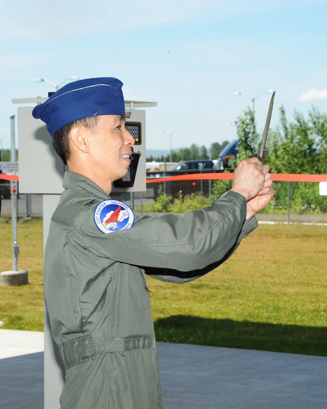 Col. Jeff Hwang, 142nd Fighter Wing Vice Commander, cuts the tape to officially open the new base Service Station, June 5, 2014 at the Portland Air National Guard Base.  (Air National Guard photo by Tech. Sgt. John Hughel, 142nd Fighter Wing Public Affairs/Released)