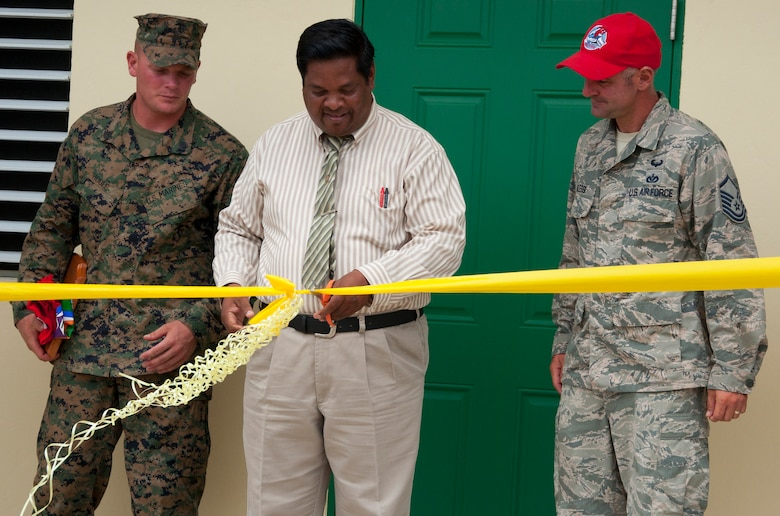 Rodrick Cardinez, Edward P. Yorke school principal, center, cuts the ribbon to officially open the school addition with U.S. Marine Corps Staff Sgt. Matt Houle, construction site foreman, left, and U.S. Air Force Master Sgt. Nicholas Alessi, construction site project manager, right, during the ribbon cutting ceremony June 4, 2014, at the school in Belize City, Belize. The school's 1,372 square foot, two-classroom addition is one of five New Horizons projects constructed in the country. New Horizons is an annual multinational exercise that provides training opportunities in civil engineering and medical care. (U.S. Air Force photo by Tech. Sgt. Kali L. Gradishar/Released)