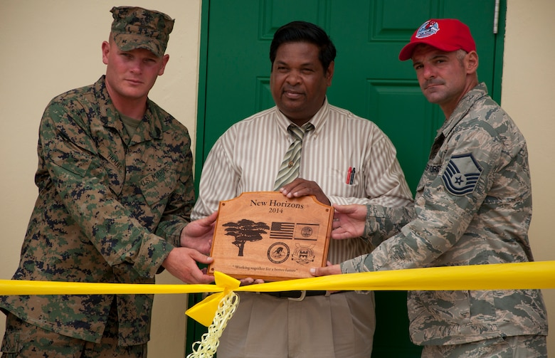 U.S. Marine Corps Staff Sgt. Matt Houle, construction site foreman, left, and U.S. Air Force Master Sgt. Nicholas Alessi, construction site project manager, right, present a plaque to Rodrick Cardinez, Edward P. Yorke school principal, during the ribbon cutting ceremony June 4, 2014, at the school in Belize City, Belize. The school's 1,372 square foot, two-classroom addition is one of five New Horizons projects in the country. New Horizons is an annual multinational exercise that provides training opportunities in civil engineering and medical care. (U.S. Air Force photo by Tech. Sgt. Kali L. Gradishar/Released)