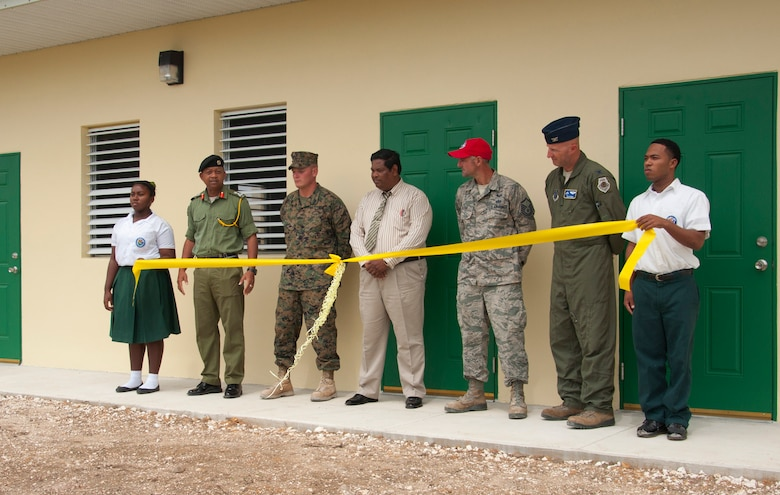One each end, an Edward P. Yorke student holds a yellow ribbon as, from left, Belize Defence Force Gen. David Jones, BDF commander, U.S. Marine Corps Staff Sgt. Matt Houle, construction site foreman, Rodrick Cardinez, E.P. Yorke principal, U.S. Air Force Master Sgt. Nicholas Alessi, construction site project manager, and U.S. Air Force Col. Dan Pepper, New Horizons Task Force commander, participate in the ribbon cutting ceremony at the school June 4, 2014, in Belize City, Belize. The school's 1,372 square foot, two-classroom addition is one of five New Horizons projects in the country. New Horizons is an annual multinational exercise that provides training opportunities in civil engineering and medical care. (U.S. Air Force photo by Tech. Sgt. Kali L. Gradishar/Released)
