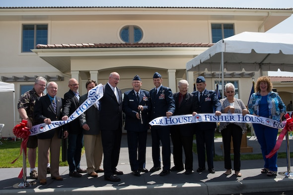 Brig. Gen. Charles Potter, center, Air Force assistant surgeon general, cuts a ribbon to formally open Fisher House II May 30 at Travis. Base leaders, Fisher House organizers and numerous distinguished visitors from the community celebrated the oepning of the home that will provide a place of comfort for military members, veterans and their families who are enduring health-related hardships. (U.S. Air Force photo/Ken Wright)