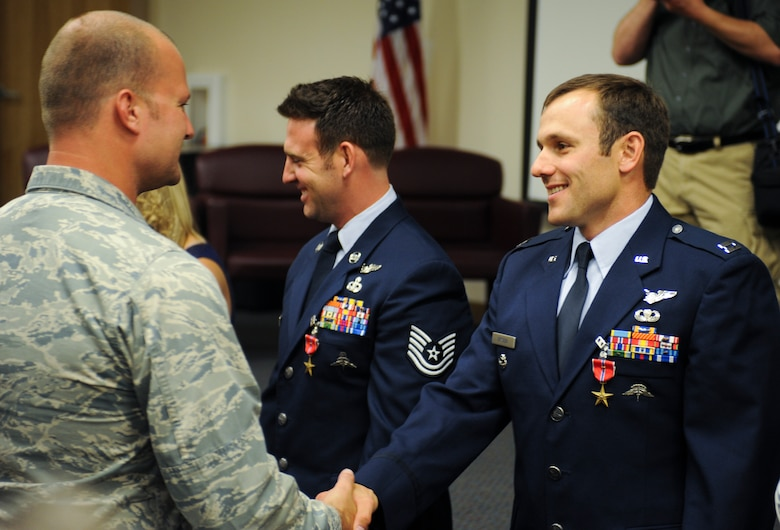 Desert Lightning Team members congratulate U.S. Air Force Capt. Kevin Epstein, 48th Rescue Squadron combat rescue officer, and Tech. Sgt. Brandon Daugherty, 306th Rescue Squadron pararescueman, for receiving a Bronze Star Medal with valor at Davis-Monthan Air Force Base, Ariz., June 2, 2014. On Feb. 2, 2012, Epstein and Daugherty engaged in a combat rescue mission that led to the rescue of Michael Stringer. (U.S. Air Force photo by Senior Airman Sivan Veazie/Released)