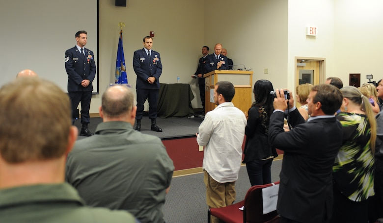 U.S. Air Force Capt. Kevin Epstein, 48th Rescue Squadron combat rescue officer, and Tech. Sgt. Brandon Daugherty, 306th Rescue Squadron pararescueman, receive a standing ovation during a Bronze Star presentation at Davis-Monthan Air Force Base, Ariz., June 2, 2014. During their deployment in Afghanistan, Epstein and Daugherty risked their lives in order to save a Marine's life. (U.S. Air Force photo by Senior Airman Sivan Veazie/Released)