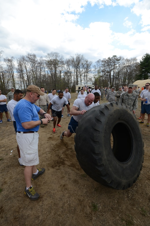 Senior Master Sgt. John Gasiorek keeps a close eye on his watch, tracking the time it takes for the 103rd Maintenance Squadron team, led by Staff Sgt. Davitt Keenan, to flip the massive tractor tire down the course and around the cone. This was a new event added to the second annual Yankee Warrior Day that took place May 3, 2014, at Bradley Air National Guard Base, East Granby, Conn. (U.S. Air National Guard photo by Tech. Sgt. Joshua Mead)