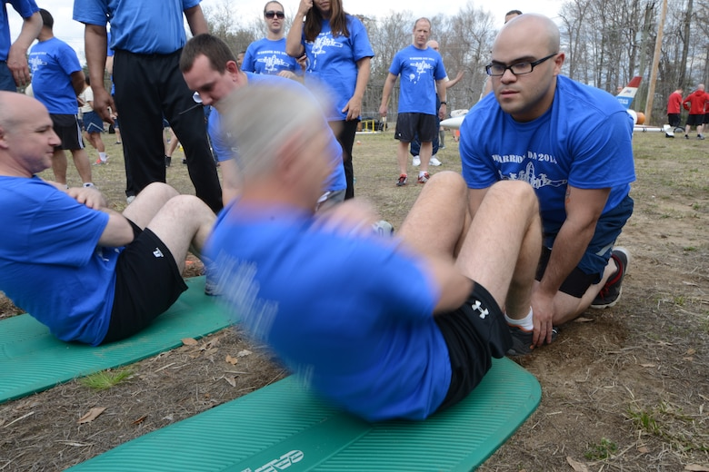 Senior Airman Emmanuel Santiago, 103rd Public Affairs photo journalist, holds the feet of Lt. Col. James Guerrera, executive officer with the 103rd Airlift Wing, as he tries to get as many sit-ups accomplished as he can during the second annual Yankee Warrior Day. The event which was held on May 3, 2014, at the Bradley Air National Guard Base, East Granby, Conn., allowed Airmen an opportunity to compete against each other during various events for a chance at winning a trophy. (U.S. Air Force photo by Tech. Sgt. Joshua Mead)