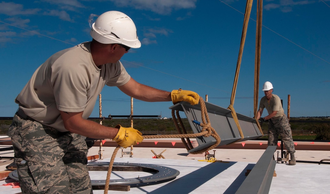 HOLT NAVAL COMMUNICATION STATION, Australia -- Master Sgt. Bryan Spake (left), operations manager for the Alaska Air National Guard's 176th Civil Engineer Squadron, and Senior Master Sgt. Scott Belyea, the squadron's structures flight chief, maneuver a steel girder into place here May 12, 2014. The pair were among 34 Alaska Air National Guard members who deployed for three weeks to this remote base in Western Australia to prepare it to receive a space radar antenna. National Guard photo by Capt. John Callahan.