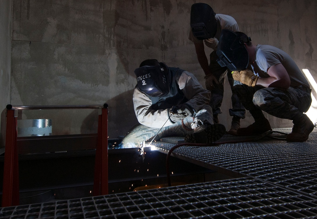 HAROLD E. HOLT NAVAL COMMUNICATION STATION, Australia -- Tech Sgt. Mark Smith, structures supervisor for the Alaska Air National Guard's 176th Civil Engineering Squadron, demonstrates welding techniques to two junior Airmen here May 6, 2014. The three were among 34 Guard members deployed here for three weeks to prepare the site to receive a space radar antenna being relocated from the Caribbean Island of Antigua. National Guard photo by Capt. John Callahan