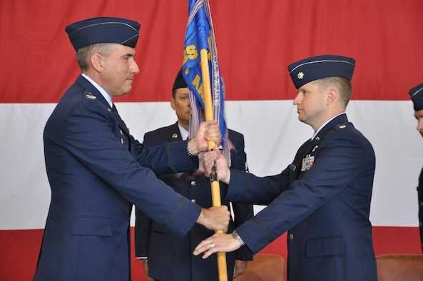 Col. John J. Cooper, 552nd Operations Group commander, left, passes the guidon to Lt. Col. Marc A. Langohr, right, signaling Colonel Langohr's assumption of command of the 964th Airborne Air Control Squadron from Lt. Col. Darren R. DeRoos during a traditional ceremony held Thursday, May 29 in Bldg. 230, Dock 2, before a host of friends, family and fellow service members. Colonel Langohr previously served as director of Operations for the 960th AACS. Colonel DeRoos will now become deputy commander to Colonel Cooper, who presided over the ceremony. (Air Force photo by Darren D. Heusel)
