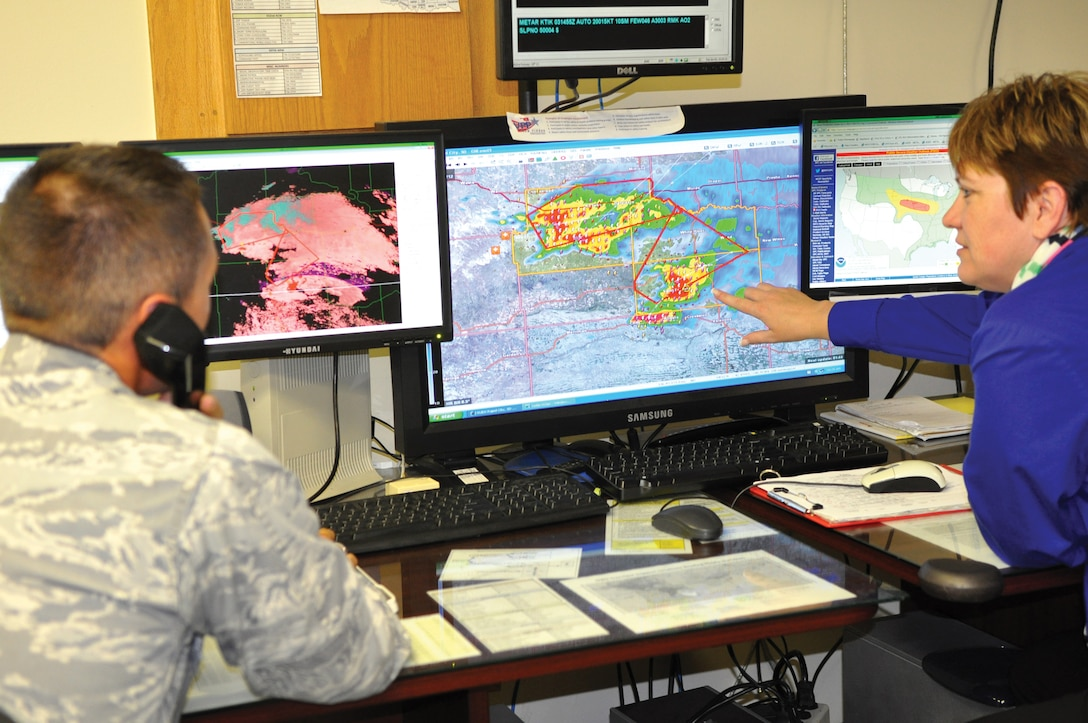 1st Lt. Casey Neuville, weather officer, and Tina Stott, weather technician, both with the 72nd Operations Support Squadron's Weather Flight, monitor and analyze weather conditions on Tinker Air Force Base.  They keep in contact with the National Weather Service and the 26th Operational Weather Squadron to collaborate the best operational weather decisions are made. (Air Force photo by Kimberly Woodruff)