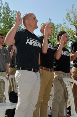 Patrick (left) and Taylor Affolder (center), recent recruits of the 122nd Fighter Wing, Fort Wayne Air National Guard Base, raise their hands for the Oath of Enlistment during a mass enlistment ceremony on May 18, 2014 at the Indianapolis Motor Speedway. The father and son duo could find no better way to begin their military careers than to enlist together at the annual ceremony held  during Armed Forces Weekend. (Air National Guard photo by Airman 1st Class Justin Andras/Released)