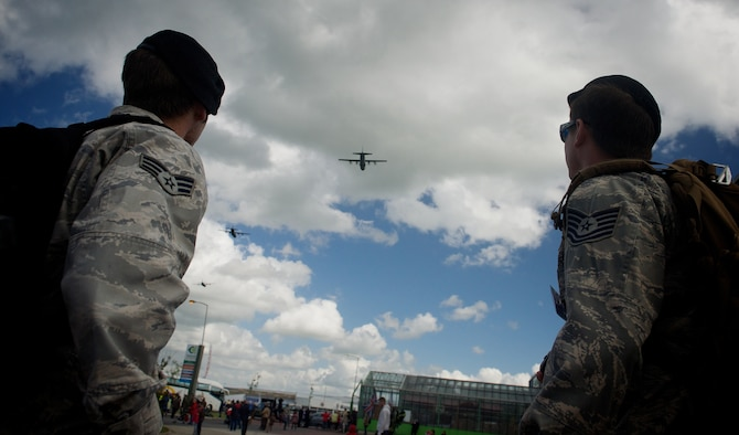 Tech. Sgt. Zachary Jacobs, right, and Senior Airman Jason Hoff watch as C-130 Hercules perform a ceremonial flyover at a 70th D-Day anniversary memorial event, June 4, 2014, in Carentan, France. Jacobs and Hoff are joint terminal attack controllers with the 116th Air Support Operations Squadron, Wash., assigned to Normandy to coordinate air movements during the events celebrating the liberation of Normandy by allied troops in 1944. (U.S. Air Force photo/Senior Airman Alexander W. Riedel)