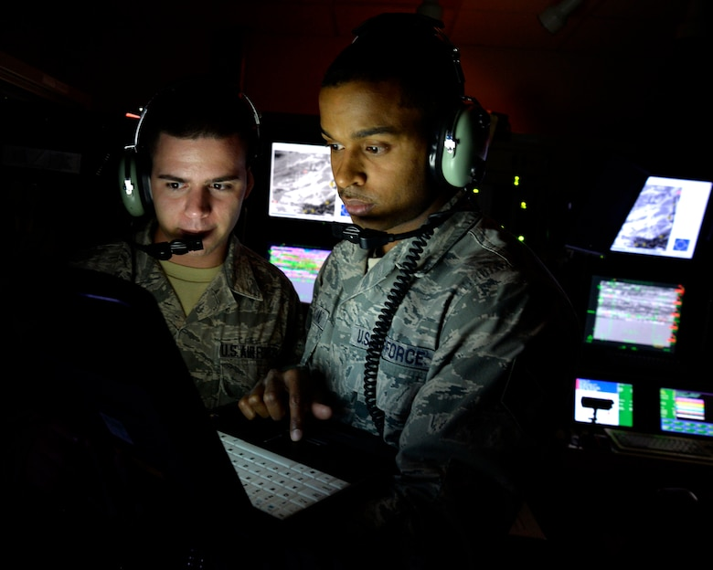 Airman First Class Ryder Luzadder, left, and Staff Sgt. Jose Feliciano look over technical orders for a ground control station May 28, 2014, at Creech Air Force Base, Nev.  Ryder and Feliciano are communications technicians with the 432nd Aircraft Communications Maintenance Squadron.  The 432nd ACMS is responsible for providing 24/7, 365-day maintenance support to the communication infrastructure that supports the wing's global remotely piloted aircraft operations. (U.S. Air Force photo/Staff Sgt. Adawn Kelsey)