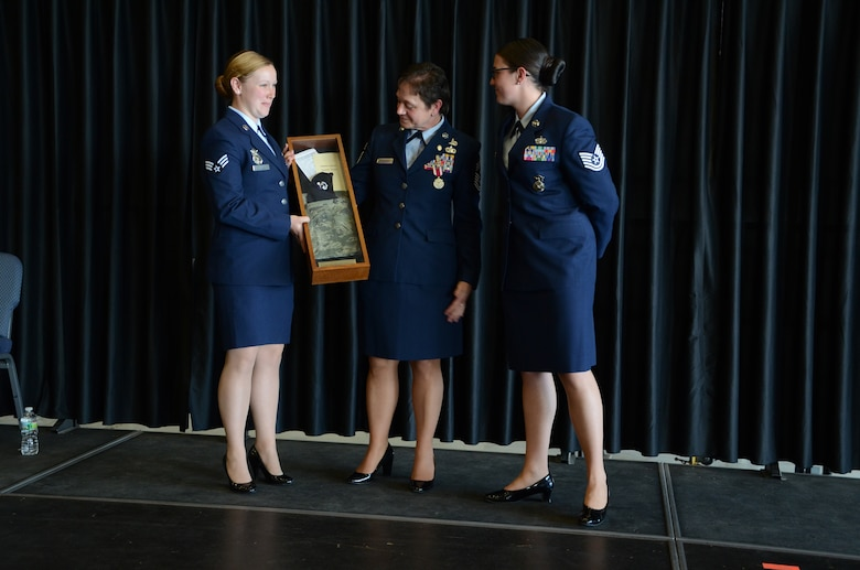 PEASE AIR NATIONAL GUARD BASE, N.H. -- Senior Airman Kelsey Hannafin and Tech. Sgt. Kristina Johnson, both members of the 157th Security Forces Squadron, make a presentation to Chief Master Sgt. Brenda Blonigen during a retirement ceremony in Hanger 254 at Pease Air National Guard Base June 7. The presentation was made to recognize the chief as a former security police member. (U.S. Air Force photo by Tech. Sgt. Mark Wyatt)