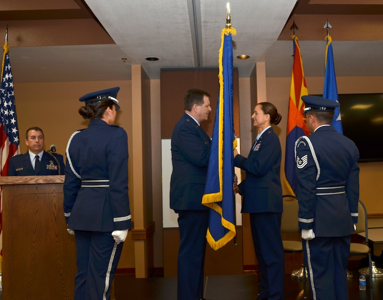 U.S. Air Force Brig. Gen. Michael McGuire, the Adjutant General of Arizona, presents Brig. Gen. Kerry L. Muehlenbeck, Arizona Army and Air Guard Joint Operations officer, a general's flag during her promotion ceremony at the 161st Air Refueling Wing, Phoenix, June 7, 2014. Brig. Gen. Muehlenbeck is the first woman to serve as a general officer in the Arizona Air National Guard. (U.S. Air National Guard photo by Senior Airman Rashaunda Williams/Released)