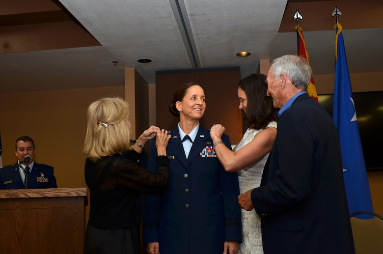 U.S. Air Force Col. Kerry L. Muehlenbeck, Arizona Army and Air Guard Joint Operations officer, is promoted to brigadier general June 7, 2014 at the 161stAir Refueling Wing, Phoenix. Her parents, Bill and Nancy Muehlenbeck, and her sister, Kelly Adams, pin on her new rank during her promotion ceremony. (U.S. Air National Guard photo by Senior Airman Rashaunda Williams/Released)