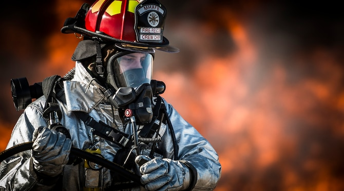A firefighter from the 366th Civil Engineer Squadron pulls a fire hose during a base-wide operation readiness exercise March 4, 2013, at Mountain Home Air Force Base, Idaho. The Mountain Home AFB Fire Department was recently awarded the 2013 Department of Defense Fire and Emergency Services of the Year award in the small fire department category. (U.S. Air Force photo/Tech. Sgt. Samuel Morse)