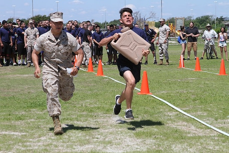 Sgt. Ivan Livia, recruiter at Recruiting Substation Ridgewood, runs next to a poolee during the water jug relay at the annual Sergeant Major's Cup field meet at Jones Beach in Wantagh, N.Y., June 7.