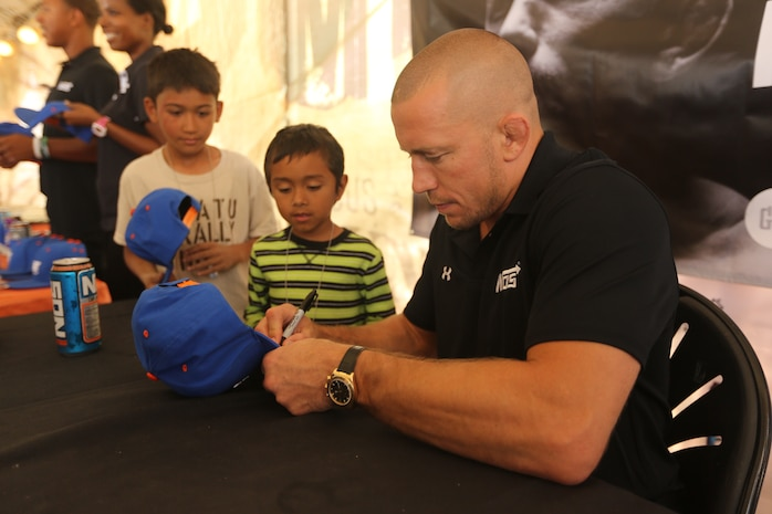 Georges St-Pierre, mixed martial artist and UFC world champion, meets Marine volunteers and runners at the 22nd World Famous Mud Run on Camp Pendleton June 8. St-Pierre took photos and signed autographs for Mud Run racers and service members during the visit.