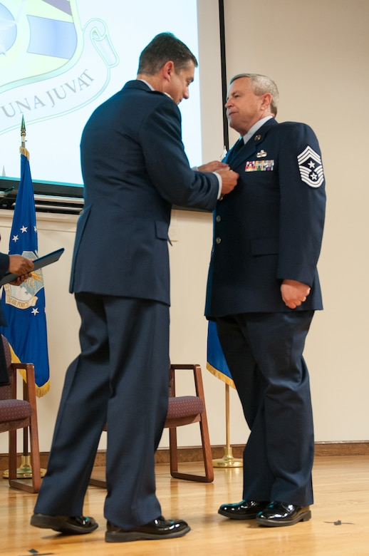 Col. Warren Hurst (left), Kentucky's assistant adjutant general for Air, pins the Meritorious Service Medal on Chief Master Sgt. Curtis R. Carpenter, outgoing 123rd Airlift Wing command chief, during Carpenter's retirement ceremony at the Kentucky Air National Guard Base in Louisville, Ky., on May 17, 2014. Carpenter served in the active-duty Air Force and Air National Guard for more than 34 years. (U.S. Air National Guard photo by Airman 1st Class Joshua Horton)