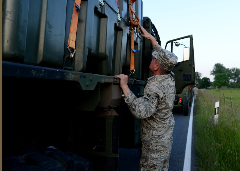 U.S. Air Force Gerremy Fearson, 606th Air Control Squadron power production apprentice, Spangdahlem Air Base, Germany, tightens cargo straps during a convoy to Poland, June 2, 2014. The convoy arrived at Powidz Air Base, Poland, to support the U.S Aviation Detachment during Exercise EAGLE TALON and Av-Det Rotation 14-3. The Av-Det was chartered to increase partnership capacity with Poland and other NATO allies through theater security cooperation events. (U.S. Air Force photo by Airman 1st Class Kyle Gese/Released)