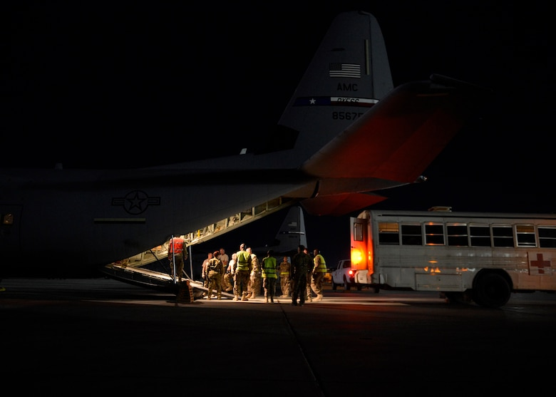 U.S. Air Force Airmen from the 455th Expeditionary Aeromedical Evacuation Squadron prepare to unload patients from a C-130J Super Hercules, Bagram Airfield, Afghanistan, May 29, 2014. The unit uses the C-130J to achieve larger patient loads, long-distance transportation, and a greater ability to care for injured members. To do this, all members of an AE crew must coordinate quickly to set up the appropriate litter configuration that maximizes patient transport and can accommodate the necessary medical equipment.  (U.S. Air Force photo by Staff Sgt. Evelyn Chavez)