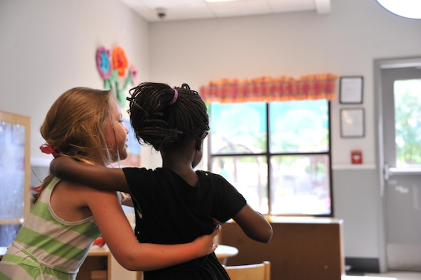 Sarah Caton, left, hugs her best friend Fatou Gueye May 20, 2014, at the Maxwell Air Force Base child development center, Ala. Both girls are 4-year-old students at the center. When Fatou, who is from Senegal, first arrived to the CDC she did not speak English, and was unfamiliar with American customs. Thanks to Sarah, Fatou is now fluent in English and has adjusted to American practices. Many foreign students attend the Maxwell CDC as their parents go through officer schools at the Air University. (U.S. Air Force photo/Staff Sgt. Natasha Stannard)