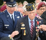A defense attaché escorts World War II veteran Edward Oleksak, who was present during the D-Day landings 70 years ago, to his seat during a D-Day Remembrance Ceremony.