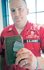 Capt. Casey Wolfe, commander, CGMCG, holds a Bible and dogtags that belonged to his grandfather, Staff Sgt. Thomas Dittmer.