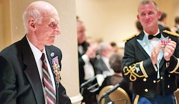 """James A. """"Jacque"""" Michienzi stands to be recognized by fellow 1st Inf. Div. Soldiers during the 95th annual Officers of the 1st Inf. Div. dinner April 26 in Alexandria, Va."""