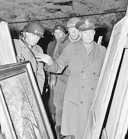Gen. Dwight D. Eisenhower, Supreme Allied commander, accompanied by Gen. Omar N. Bradley and Lt. Gen. George S. Patton Jr., inspects art treasures stolen by Germans and hidden in salt mine in Germany April 12, 1945.