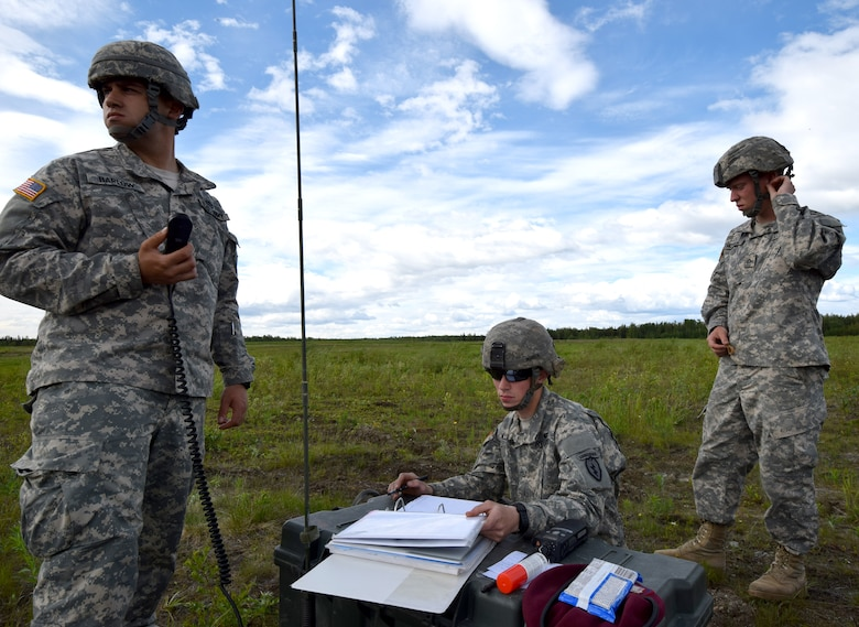 Soldiers with the 4th Infantry Brigade Combat Team (Air Borne), 25th Infantry Division coordinate with incoming paratroopers  on Joint Base Elmendorf-Richardson, Alaska, as part of a Joint Force Entry Exercise on June 7, 2014. The six-day exercise involved over 1,500 personnel including active duty Army, Air Force and Air National Guard. ( U.S. Air National Guard photo by Captain John Callahan/ Released)