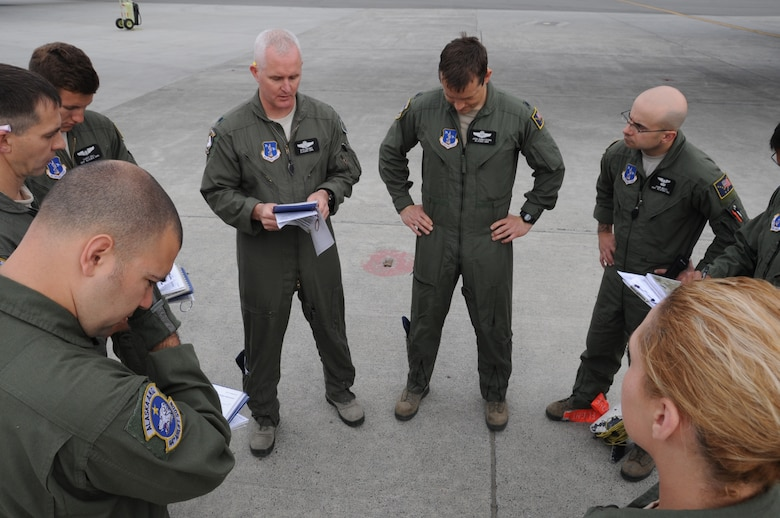 Aircrew members from the 144th Airlift Squadron hold a final briefing prior to take-off Joint Base Elmendorf-Richardson, Alaska, for an airdrop as part of a six-day Joint Forcible Entry Exercise on June 7, 2014. The JFEX was a joint effort between active duty Army, Air Force and Air National Guard units from Alaska, Washington and Guam. (Air Force photo by Staff Sgt. William Banton/ Released)