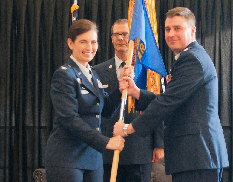 U.S. Air Force Lt. Col. Bradley Stevens, Commander, 64th Air Refueling Squadron (right) , accepts the 64 ARS guideon from U.S. Air Force Col. Jennifer Uptmor (left), Commander, 22nd Operations Group, McConnell Air Force Base, K.A. signifying his assuming command, Pease ANGB, June 8, 2014.