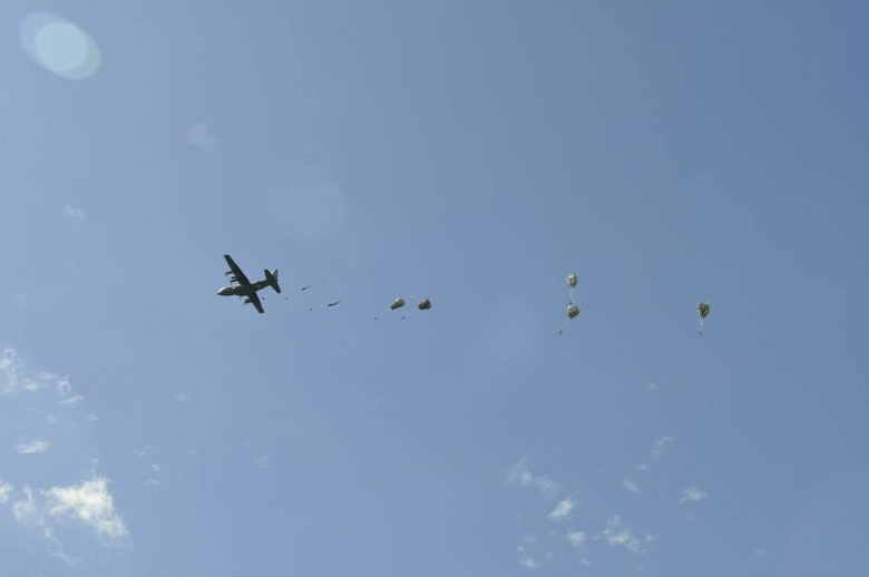 """A Nevada Air National Guard C-130 drops paratroopers over the """"Iron Mike"""" Drop Zone outside Sainte-Mère-Église, France as part of the June 6, 1944 D-Day commemoration. 14 different airplanes, to include 2 from the Nevada Air National Guard, dropped over 700 paratroopers as part of the ceremony. (USAF Photo by Capt. Jason Yuhasz, 152nd Airlift Wing Public Affairs/RELEASED.)"""