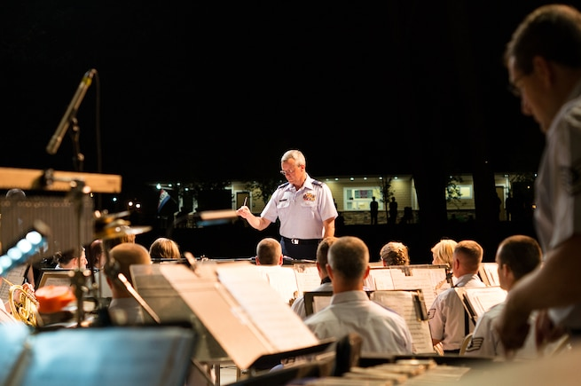 Commander Major Roger Mills conducts the concert band during a performance