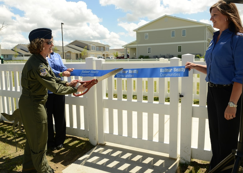Col. Marné Deranger, 341st Missile Wing vice commander, cuts a ribbon during the grand opening of Malmstrom's first dog park, sponsored by Balfour Beatty Communities. The dog park includes a large park and a separate park small dogs. (U.S. Air Force photo/Senior Airman Katrina Heikkinen)