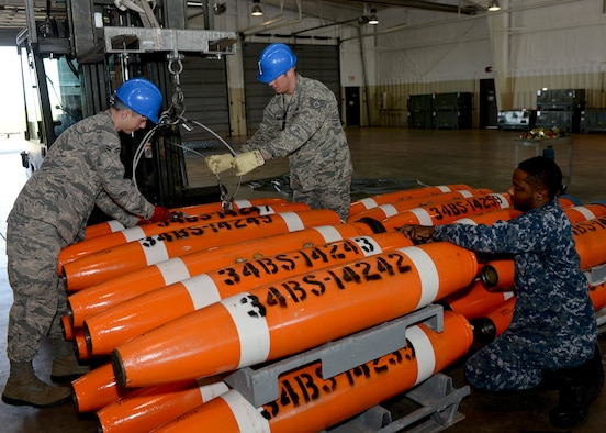 Staff Sgt. Raymond Elmendorf and Airman 1st Class Eric Morrison, 28th Munitions Squadron conventional maintenance crew members, assist Petty Officer 2nd Class Dwight Moore, Naval Munitions Command Seal Beach mineman, with loading Mk-62 Quickstrike mines onto munitions carts at Ellsworth Air Force Base, S.D., June 2, 2014. (Air Force photo/Senior Airman Anania Tedurio)