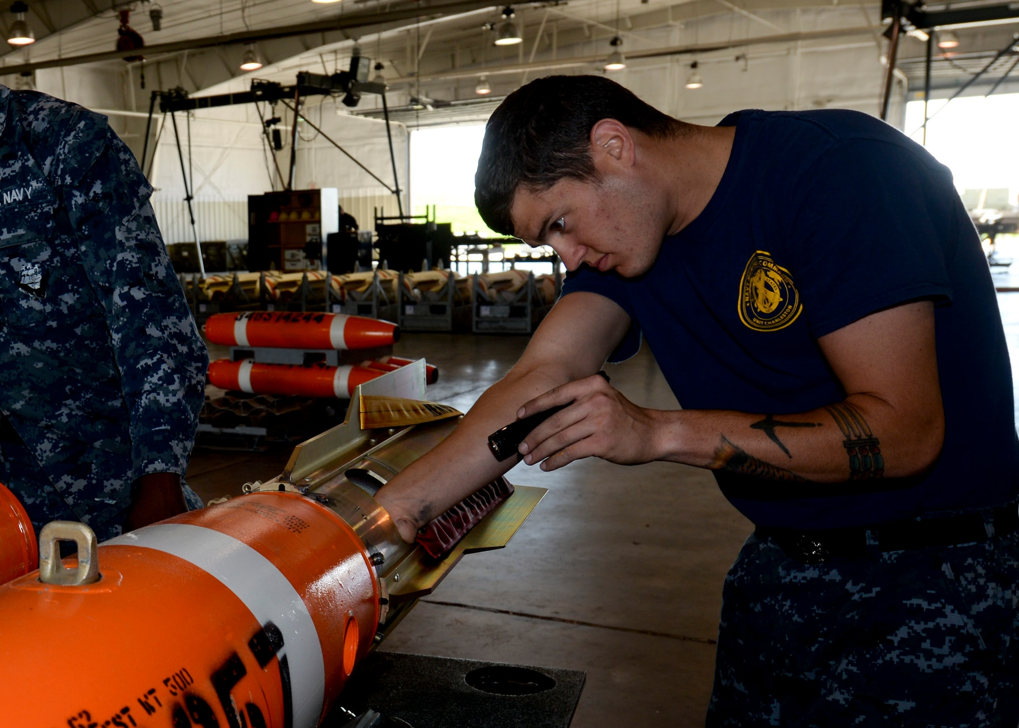 Petty Officer 2nd Class Daniel Bentley, Naval Munitions Command Charleston mineman, adjusts the fin assembly on an Mk-62 Quickstrike mine at Ellsworth Air Force Base, S.D. June 2, 2014. The B-1B Lancer pilots dropped the mines at an altitude of about 1,000 feet while moving at more than 500 kilometers an hour as part of a joint exercise with Ellsworth Airmen designed to enhance air and sea capabilities. (U.S. Air Force photo by Senior Airman Anania Tekurio)
