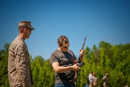 A civilian Marine who works in the Program and Resources Office at Headquarters Marine Corps learns about different small arms before doing live at Weapons Training Battalion. Employees from P&R visited Quantico June 6, to better understand how their work impacts Marines in the fleet.