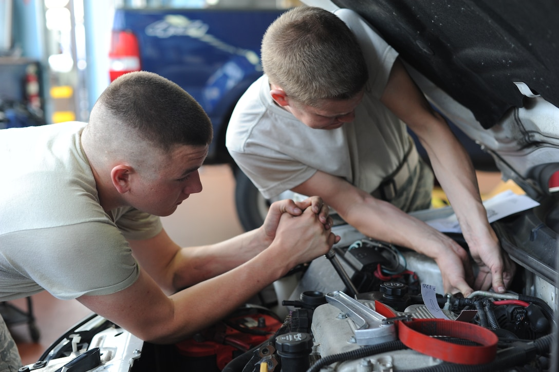 U.S. Air Force Airman 1st Class Garrett Goss, from Port Matilda, Pa., left, and Airman Christian Bell, from Montgomery, Ala., both 52nd Logistics Readiness Squadron vehicle mechanics, work to replace a serpentine belt and water pump June 10, 2014, at Spangdahlem Air Base, Germany. All government vehicles assigned to the 52nd Fighter Wing come in for maintenance every 18 months. (U.S. Air Force photo by Airman 1st Class Dylan Nuckolls/Released)