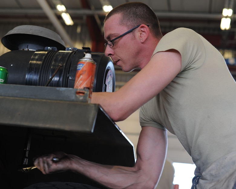 U.S. Air Force Staff Sgt. Randy Johnson, a 52nd Logistics Readiness Squadron special purpose vehicle mechanic from Newark, Ohio, works to pull the motor from an aircraft-towing vehicle June 10, 2014, at Spangdahlem Air Base, Germany. The 52nd LRS Vehicle Management Flight's mechanics perform routine tasks such as oil changes to complete engine repairs. (U.S. Air Force photo by Airman 1st Class Dylan Nuckolls/Released)