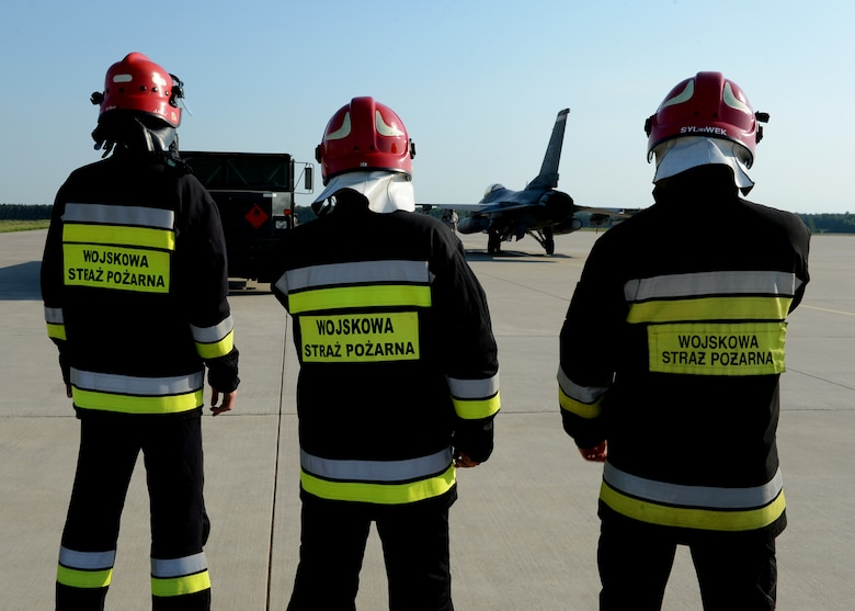 Polish fire rescue men stand watch over U.S. Air Force F-16 Fighting Falcon fighter aircraft refueling operations at a hot refueling pit at Lask Air Base, Poland, June 9, 2014. During Polish-led EAGLE TALON and U.S. Navy-led BALTOPS 14, NATO allies worked together to increase interoperability and mission effectiveness while maintaining security in Eastern Europe.This is the first time hot pit refueling has been done in Poland by U.S. Forces. (U.S. Air Force photo by Airman 1st Class Kyle Gese/Released)