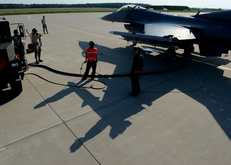 U.S. Air Force Airmen from Spangdahlem Air Base, Germany, refuel a returning U.S. Air Force F-16 Fighting Falcon fighter aircraft at Lask Air Base, Poland, June 9, 2014. The Polish Air Force refuels aircraft during the daily flying operations, while the U.S. Air Force executes hot pit refueling, which shortens the flying window and increases capability to fix aircraft in a timely manner. This is the first time it has been done in Poland by U.S. Forces. Their efforts support Exercise EAGLE TALON, BALTOPS 14 and U.S. Aviation Detachment Rotation 14-3. (U.S. Air Force photo by Airman 1st Class Kyle Gese/Released)