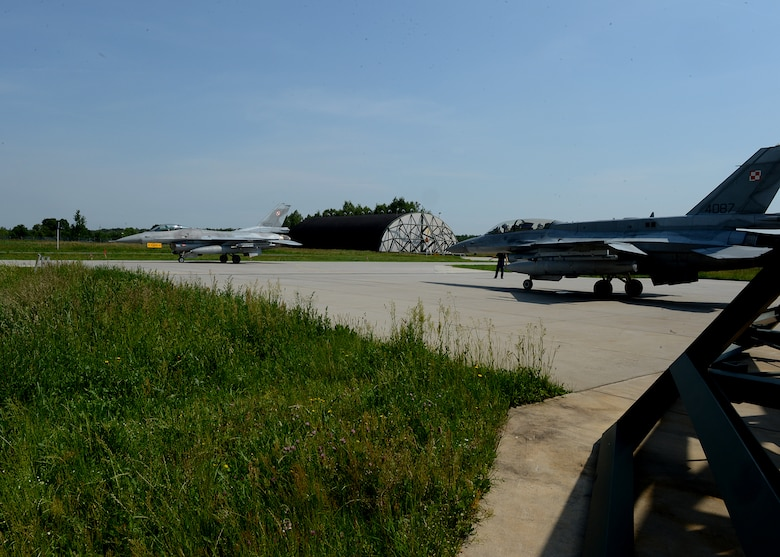 A Polish air force F-16 Fighting Falcon fighter aircraft, left, waits for another aircraft to pass before departure from Lask Air Base, Poland, June 10, 2014. Both aircraft departed to participate in exercise EAGLE TALON with NATO partners. This exercise is similar to exercise RED FLAG that takes place in Nellis Air Force Base, Nev., and Eileson Air Force Base, Ala., which provides aerial combat tactics training in a combined environment. (U.S. Air Force photo by Airman 1st Class Kyle Gese/Released)