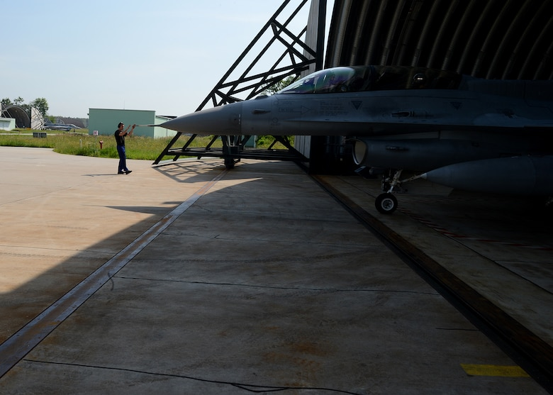 Polish air force Warrant Officer Cichecki Martin, crew chief, taxies a Polish air force F-16 Fighting Falcon fighter aircraft during Exercise EAGLE TALON at Lask Air Base, Poland, June 10, 2014. Exercise EAGLE TALON enhances pilots' abilities to operate with NATO allies, accomplish large force formations and execute air-to-air and air-to-surface missions. (U.S. Air Force photo by Airman 1st Class Kyle Gese/Released)