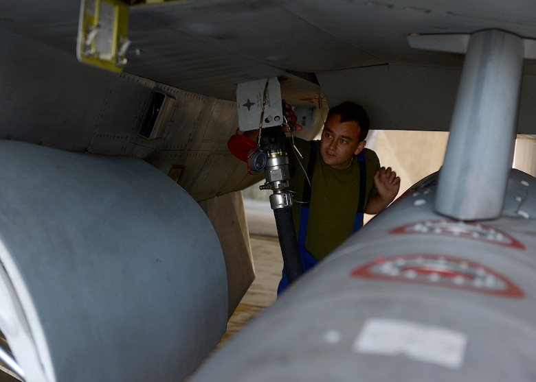 Polish air force Corporal Paliwoda Ukosz, fuels technician, refuels an aircraft before its departure, June 10, 2014, to join NATO allies in the sky above Lask Air Base, Poland. The U.S. and Polish continue to work together to refuel aircraft during Exercise EAGLE TALON, a Polish-led combined exercise. There are two shifts for refueling: day shift and night shift. The Polish Air Force refuels aircraft during the daily flying operations, while the U.S. Air Force executes hot pit refueling, which shortens the flying window and increases capability to fix aircraft in a timely manner. (U.S. Air Force photo by Airman 1st Class Kyle Gese/Released)