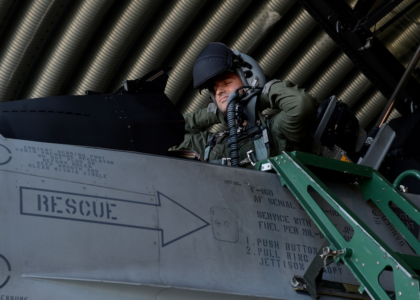 Polish air force 1st Lt. Tomasz Grzybowski, F-16 Fighting Falcon fighter aircraft pilot, puts on his helmet in preparation to fly with U.S. and NATO allies at Lask Air Base, Poland, June 10, 2014 during Exercise EAGLE TALON, a Polish-led combined exercise. This is the first time the U.S. has participated in this exercise, which trains pilots to attack and defend targets with NATO allies. Training together in partnership enhances understanding of each other's tactics and procedures for future combined operations. (U.S. Air Force photo by Airman 1st Class Kyle Gese/Released)