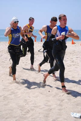 Triathletes race across the sand, transitioning from the ocean swim to the bike race.
