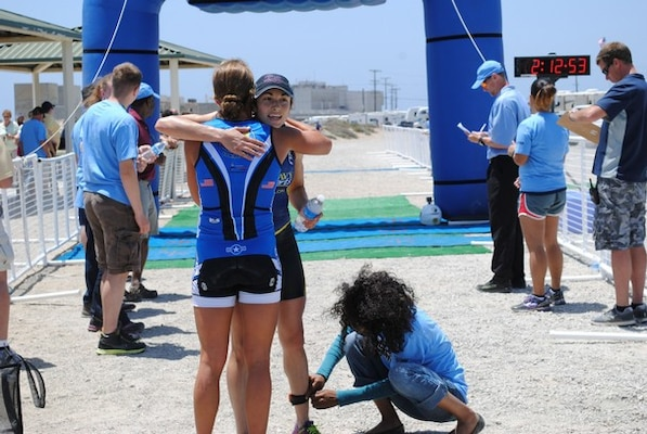 Air Force 2nd Lt. Samantha Morrison, who finished first among the women, congratulates the second-place winner as she crosses the finish line, Navy Lt. Rachel Beckman.